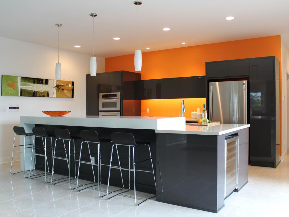 kitchen with orange accent wall black cabinets